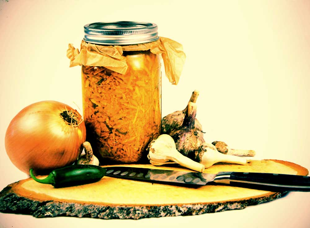 Mason jar filled with herbs and liquid on a cutting board with knife, onion, hot pepper, garlic and other herbs